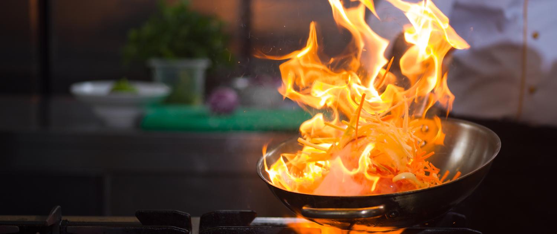 Küchenchef flambiert Gericht über dem Herdfeuer