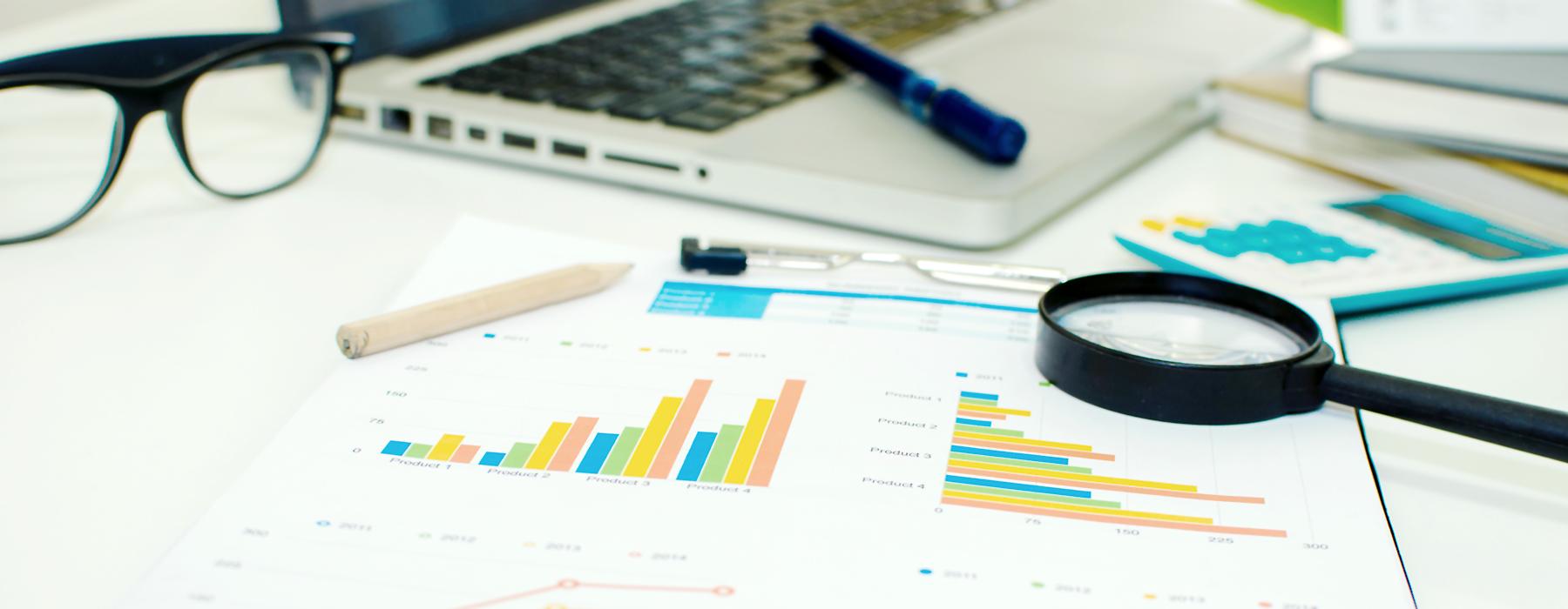 Schreibtisch mit Laptop und Büchern, Wirtschaftszahlen und Grafiken, Brille, Lupe und Stiften
