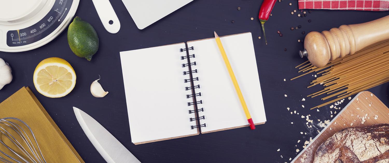 Küchenutensilien, Kochzutaten, Notizbuch und Laptop auf einer Arbeitsplatte